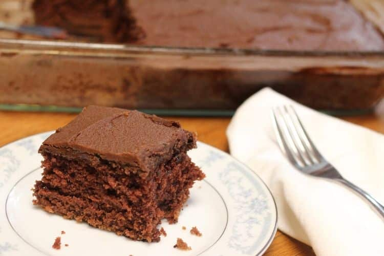 image of a slice of old fashion chocolate cake with a pan of chocolate in the background