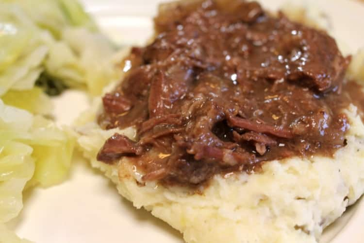 image of white plate with canned venison and gravy on top of mashed potatoes with cabbage.