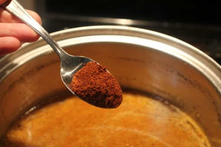 image of putting chili powder in a stock pot of chicken enchilada sauce