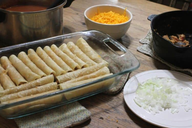 image of rolled chicken enchiladas in glass pan with enchilada sauce, chopped onion, and grated cheese surrounding them
