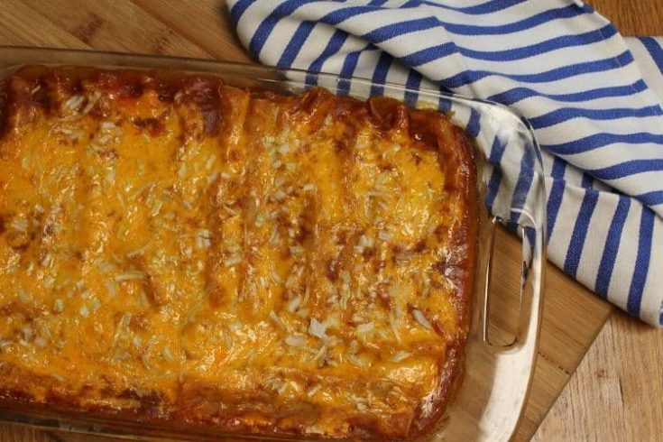 image of a glass pan of cooked chicken enchiladas with a blue and white striped kitchen towel