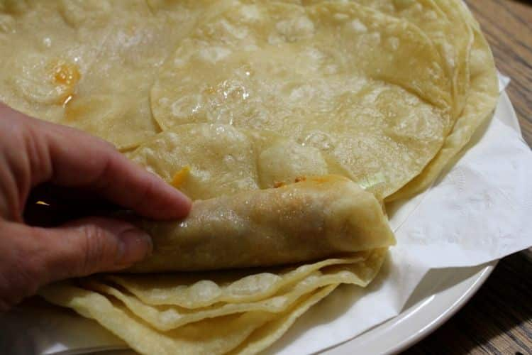 image of corn tortillas being rolled into chicken enchiladas