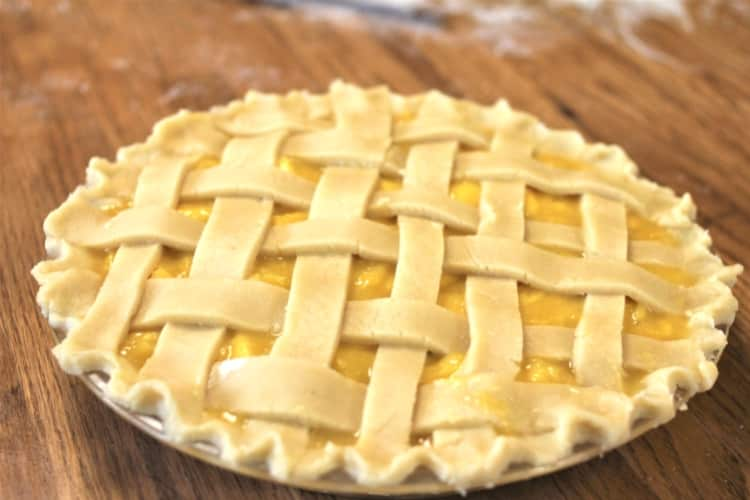 image of mango lime pie with lattice pie crust on wood table dusted with flour