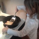 daughter helping cook pancakes