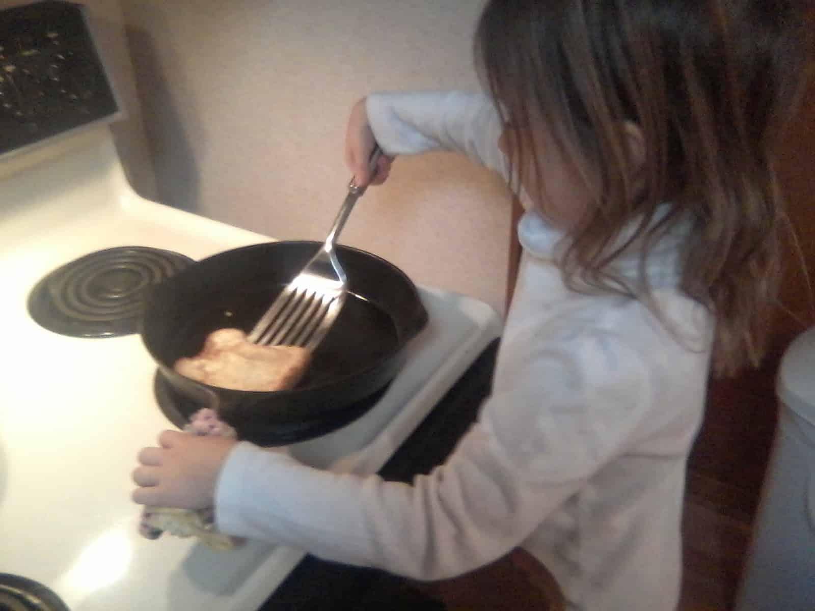 daughter helping cook pancakes
