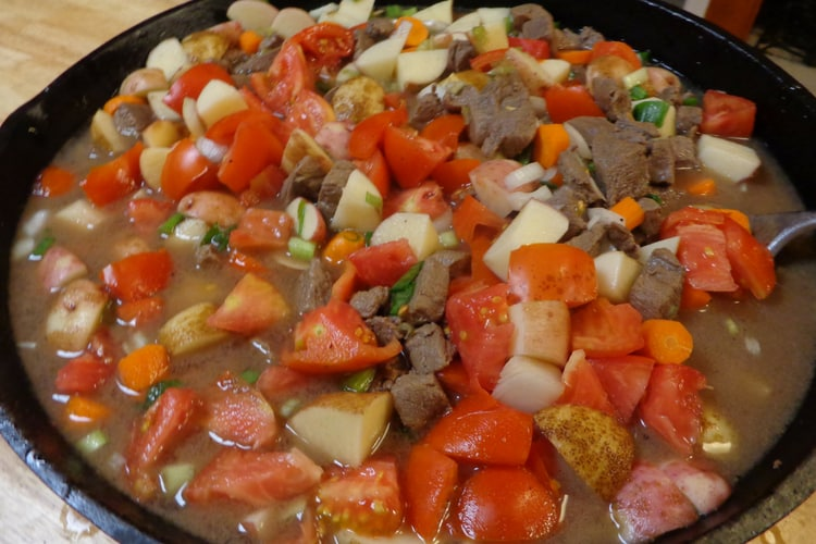 beef stew being cooked in cast iron skillet