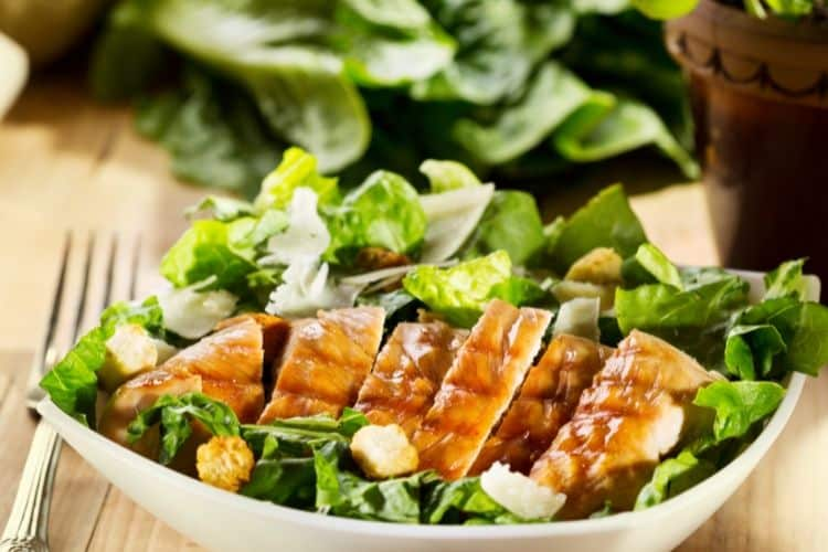 image of salad with grilled chicken in white bowl