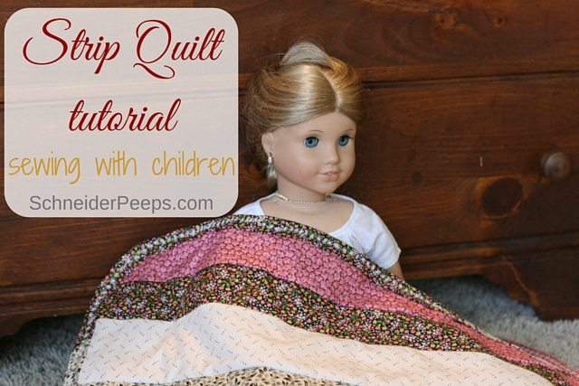 image of doll with strip quilt over it.