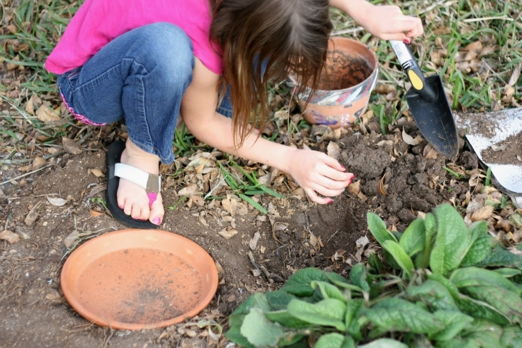 image of girl creating a frog habitat with terra cotta pots