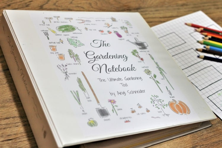Garden journal notebook with garden layout and colored pencils on wooden table.