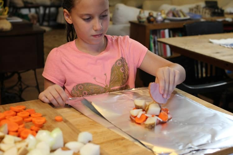 image of young girl making foil dinner packets