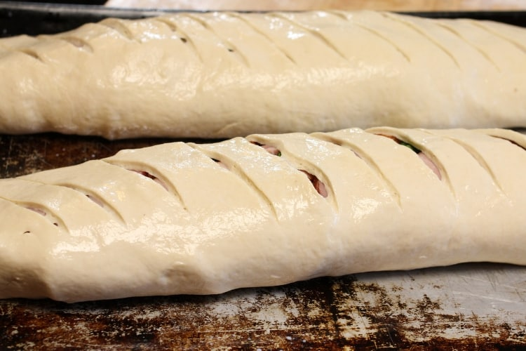 image of two stromboli on baking sheet brushed with milk before baking