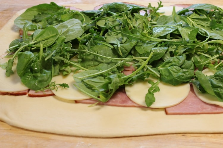 image of ham and cheese stromboli with arugula before baking