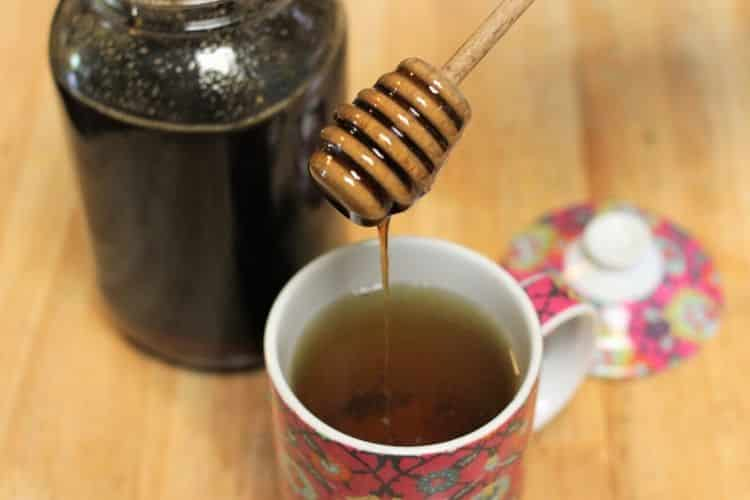 image of someone putting dark raw honey in nettle tea for allergies