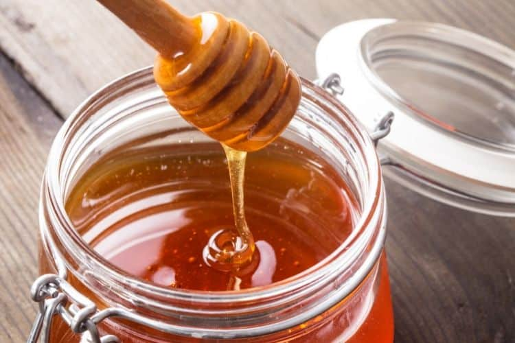 image of honey in a jar with a honey dipper
