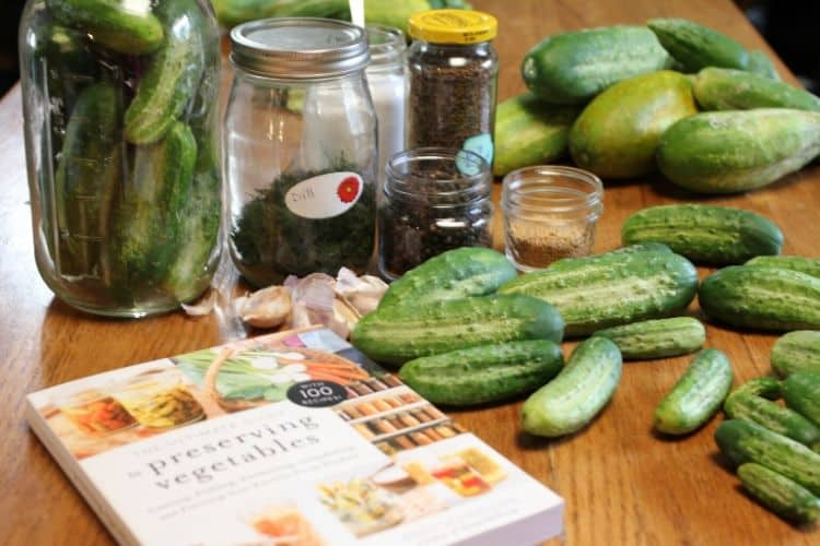 ingredients for fermenting cucumber pickles and The Ultimate Guide to Preserving Vegetables book