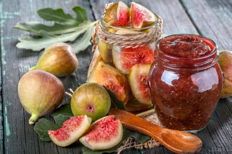 cut brown turkey figs and fig jam in glass jar