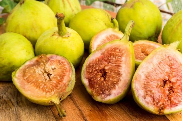 cut and whole figs on wooden cutting board